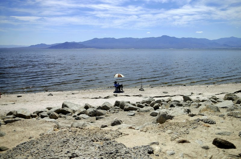 FILE - In this April 30, 2015 file photo, a man fishes for tilapia along the receding banks of the Salton Sea near Bombay Beach, Calif. (AP Photo/Gregory Bull, File)
