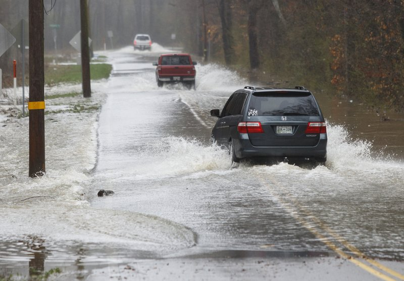 Vehicles travel through floodwaters on Boy Scout Road on Saturday, Feb. 23, 2019, in Soddy-Daisy, Tenn. (Doug Strickland/Chattanooga Times Free Press via AP)