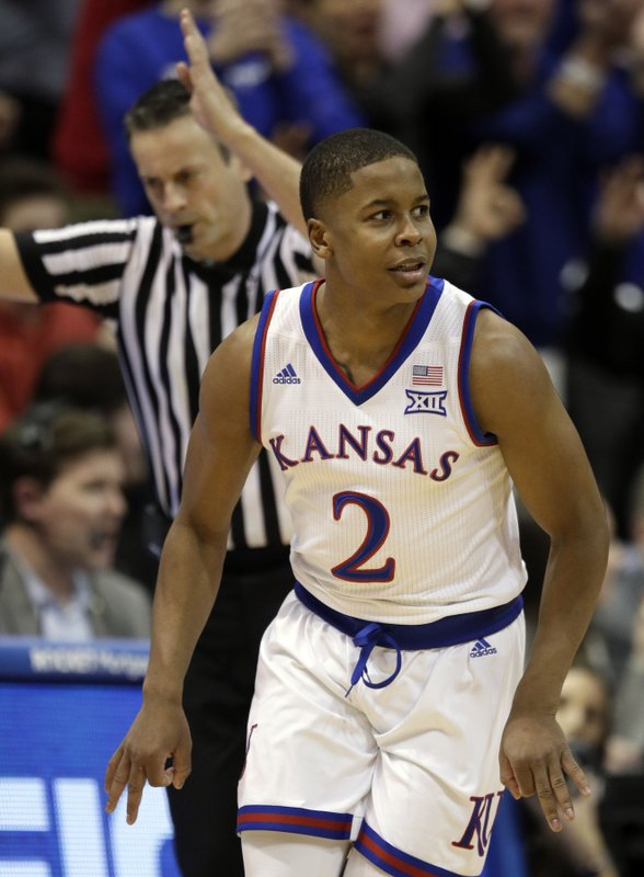 Kansas guard Charlie Moore (2) celebrates a three-point basket during the second half of an NCAA college basketball game against Kansas State in Lawrence, Kan. (AP Photo/Orlin Wagner)
