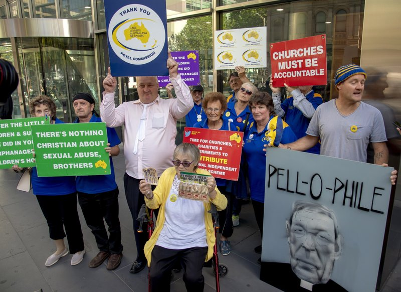 Protesters hold placards outside the County Court where Cardinal George Pell is to arrive in Melbourne, Australia, Wednesday, Feb. (AP Photo/Andy Brownbill)