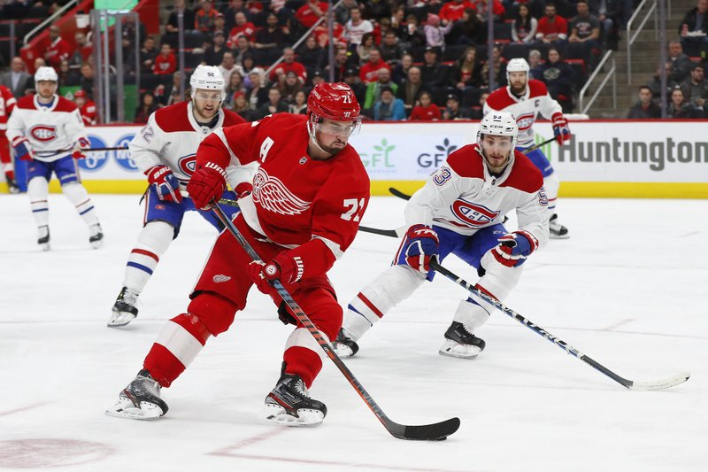 Detroit Red Wings center Dylan Larkin (71) back hands a shot against the Montreal Canadiens in the second period of an NHL hockey game, Tuesday, Feb. (AP Photo/Paul Sancya)