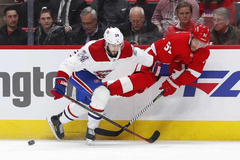 Detroit Red Wings center Frans Nielsen (51) passes as he is upended by Montreal Canadiens center Phillip Danault (24) in the first period of an NHL hockey game, Tuesday, Feb. (AP Photo/Paul Sancya)