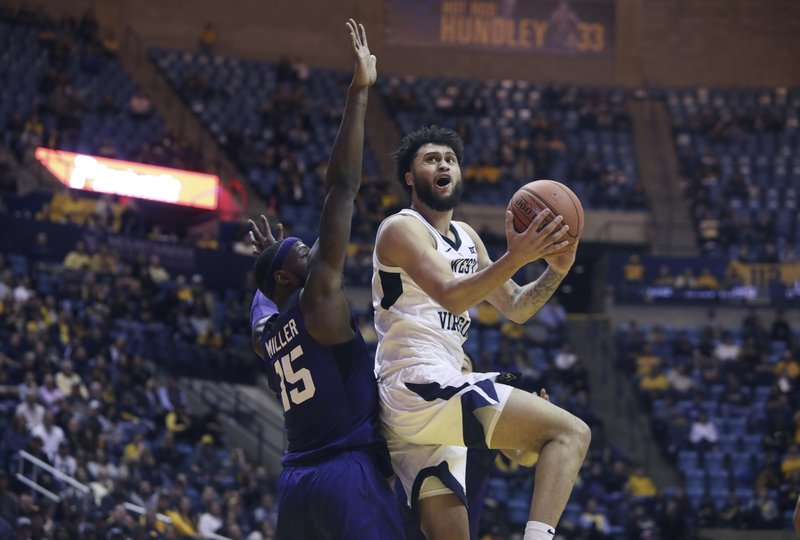 West Virginia guard Jermaine Haley (10) drive while defended by TCU forward JD Miller (15) during the first overtime of an NCAA college basketball game Tuesday, Feb. (AP Photo/Raymond Thompson)