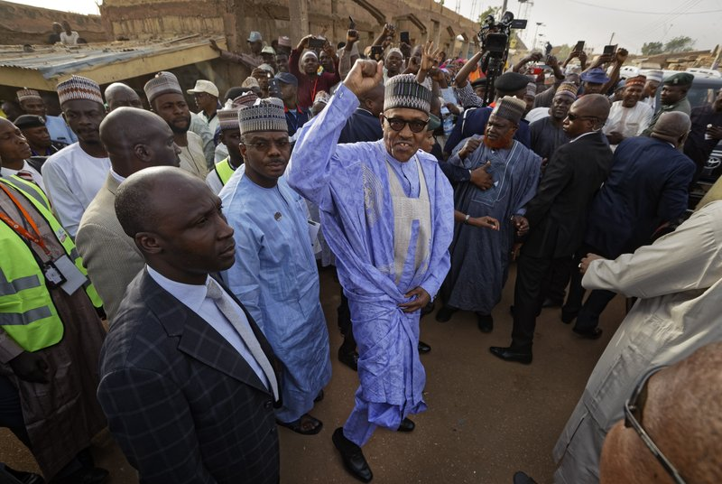 FILE - In this Saturday, Feb. 23, 2019 file photo, Nigeria's President Muhammadu Buhari gestures to supporters after casting his vote in his hometown of Daura, in northern Nigeria. (AP Photo/Ben Curtis, File)