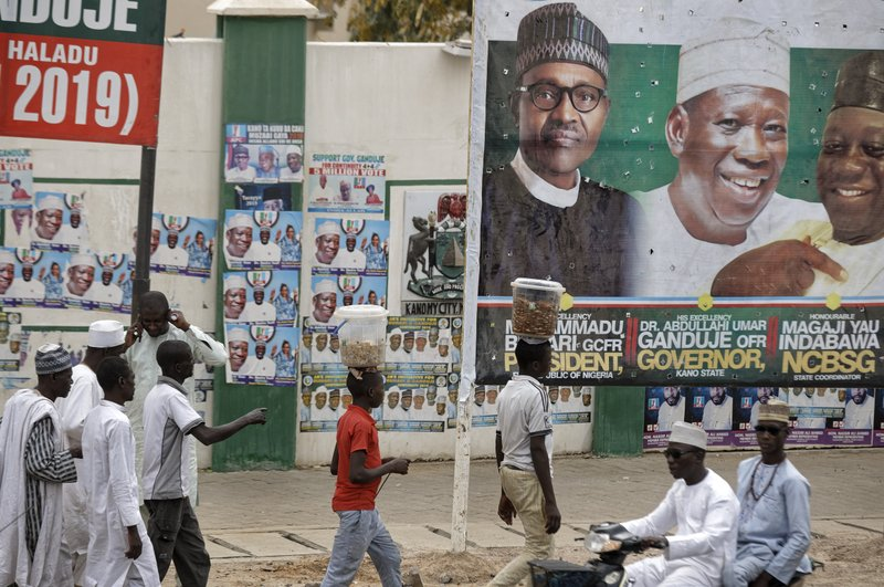 Street-vendors and others walk past a billboard showing Nigeria's President Muhammadu Buhari and other party officials, in Kano, northern Nigeria Tuesday, Feb. (AP Photo/Ben Curtis)