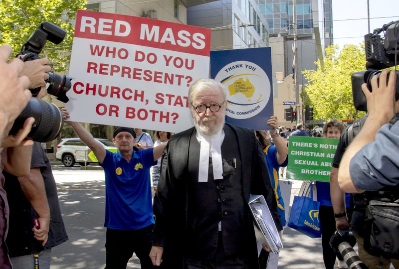 Cardinal George Pell's lawyer Robert Richter leaves the County Court as protesters hold placards in Melbourne, Australia, Wednesday, Feb. (AP Photo/Andy Brownbill)