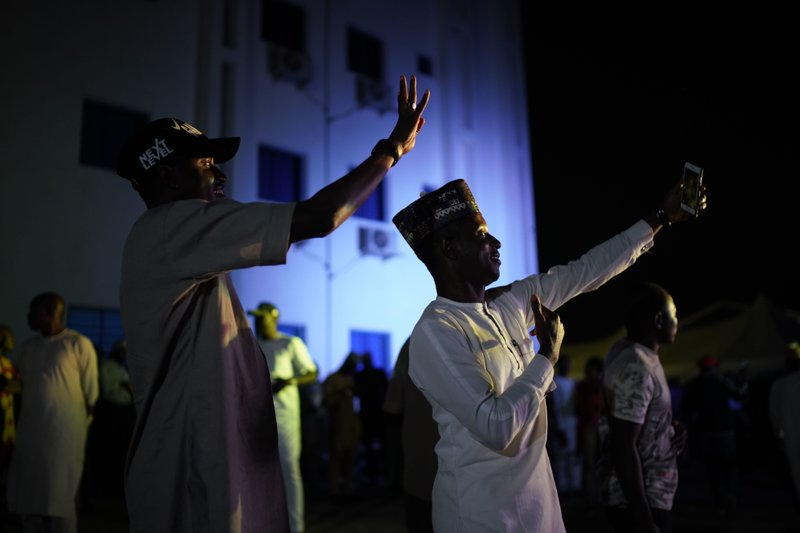 Supporters of Incumbent President Muhammadu Buhari take selfies at Buhari's campaign headquarters as they wait for the results to be officially announced in Abuja, Nigeria, Tuesday, Feb. (AP Photo/Jerome Delay)