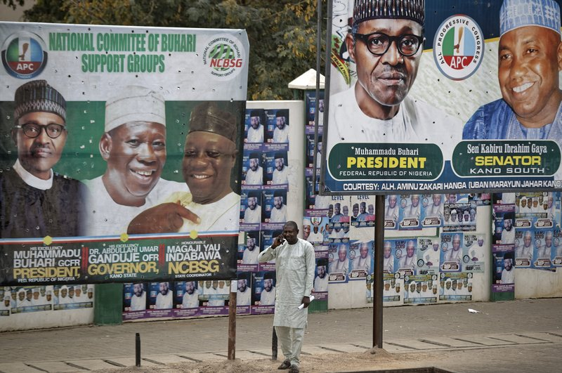 A man takes a call on his cellphone as he stands between two billboards showing Nigeria's President Muhammadu Buhari and other party officials, in Kano, northern Nigeria Tuesday, Feb. (AP Photo/Ben Curtis)