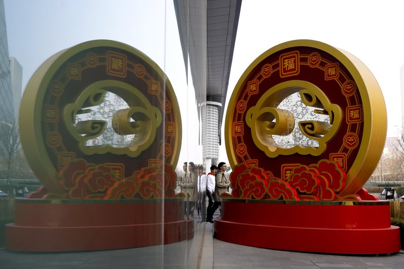 People walk by a golden prosperous pig structure on display outside a high-end commercial building at the Central Business District in Beijing, Wednesday, Feb. (AP Photo/Andy Wong)