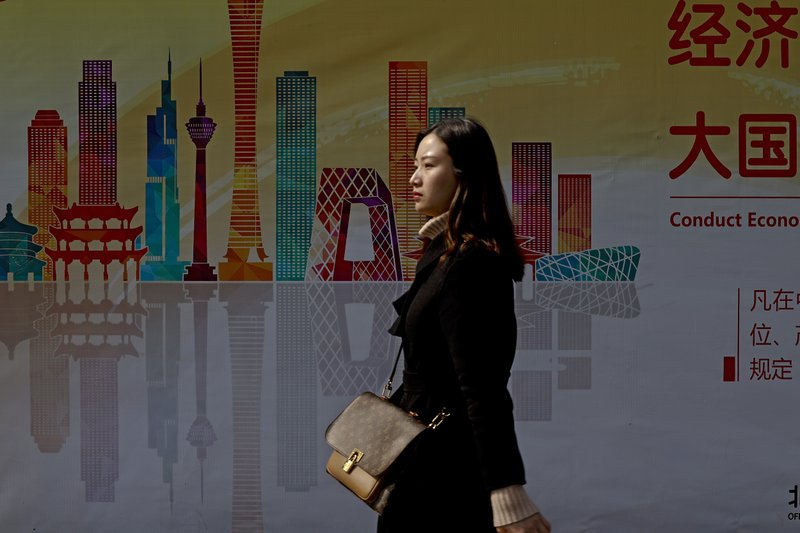 A woman walks by a billboard depicting skyscrapers in the Chinese capital at the Central Business District in Beijing, Wednesday, Feb. (AP Photo/Andy Wong)