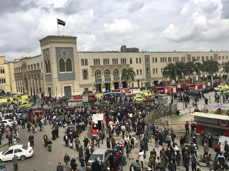 People gather outside Ramsis train station in Cairo, Egypt, Wednesday, Feb. 27, 2019. An Egyptian medical official says 20 people have been killed and dozens injured when a major fire erupted at the main train station in Cairo. (AP Photo/Nariman El-Mofty)