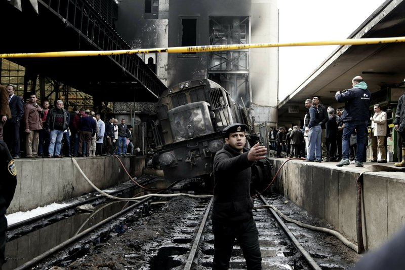 Policemen stand guard in front of a damaged train inside Ramsis train station in Cairo, Egypt, Wednesday, Feb. (AP Photo/Nariman El-Mofty)