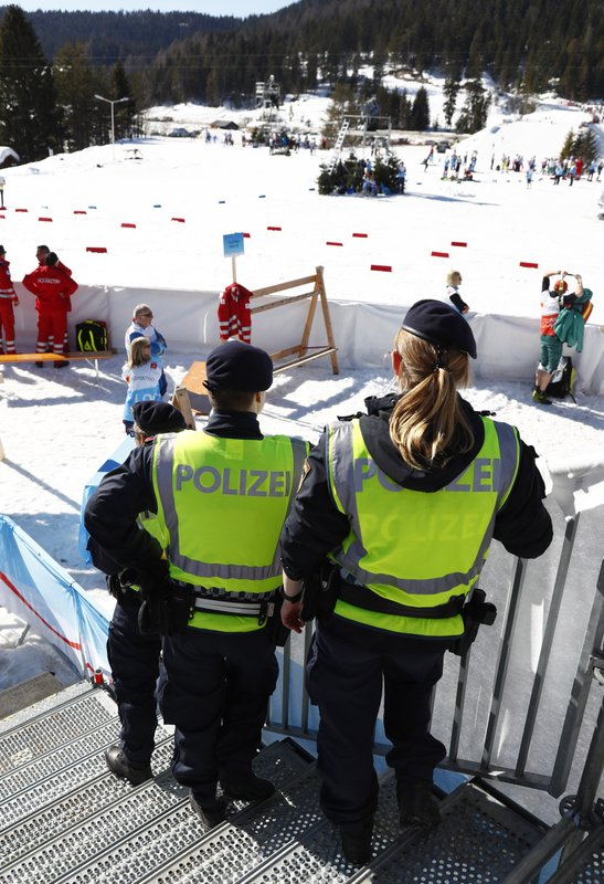 Austrian Federal Police officers stand at the finish area of a men's cross country skiing 15km classic competition, at the Nordic Ski World Championships, in Seefeld, Austria, Wednesday, Feb. (AP Photo/Matthias Schrader)