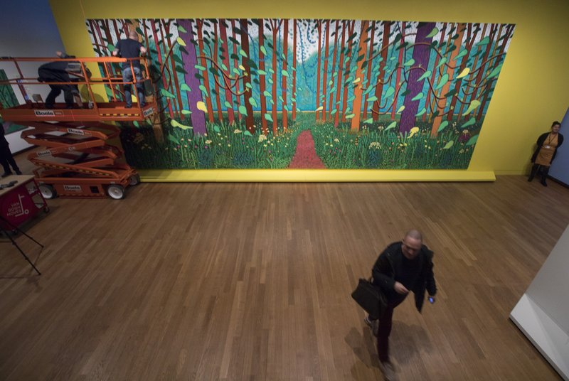 Employees of the Van Gogh Museum make last adjustments when mounting the 32-canvas painting by David Hockney titled