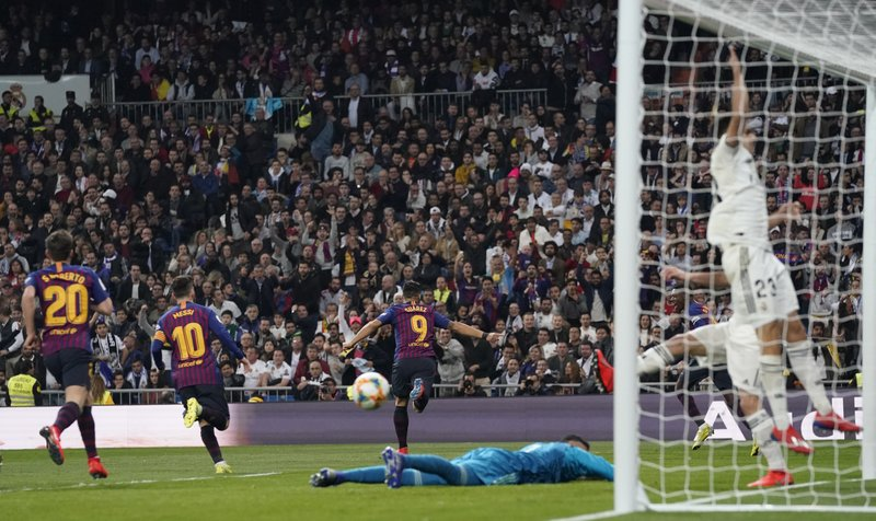 Barcelona forward Luis Suarez, center, celebrates after scoring his side's opening goal during the Copa del Rey semifinal second leg soccer match between Real Madrid and FC Barcelona at the Bernabeu stadium in Madrid, Spain, Wednesday Feb. (AP Photo/Andrea Comas)