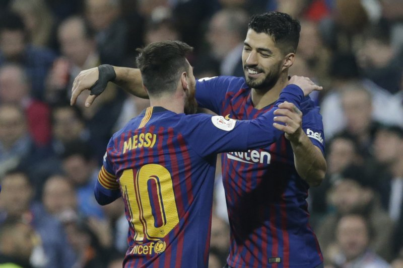 Barcelona forward Luis Suarez, right, celebrates with Barcelona forward Lionel Messi after scoring his side's opening goal during the Copa del Rey semifinal second leg soccer match between Real Madrid and FC Barcelona at the Bernabeu stadium in Madrid, Spain, Wednesday Feb. (AP Photo/Andrea Comas)