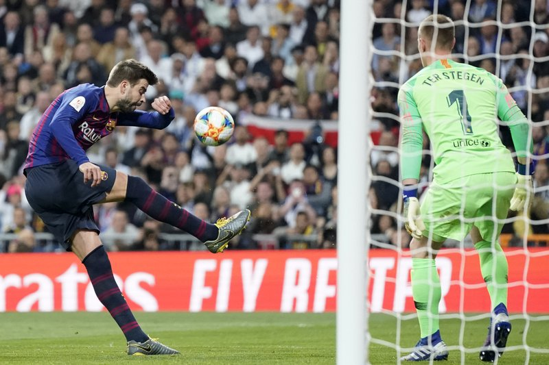Barcelona defender Gerard Pique, left, clears the ball during the Copa del Rey semifinal second leg soccer match between Real Madrid and FC Barcelona at the Bernabeu stadium in Madrid, Spain, Wednesday Feb. (AP Photo/Andrea Comas)