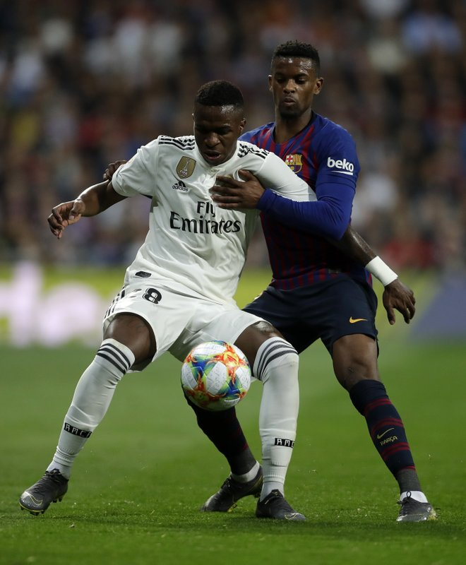 Real forward Vinicius Junior, left, and Barcelona defender Nelson Semedo challenge for the ball during the Copa del Rey semifinal second leg soccer match between Real Madrid and FC Barcelona at the Bernabeu stadium in Madrid, Wednesday, Feb. (AP Photo/Manu Fernandez)