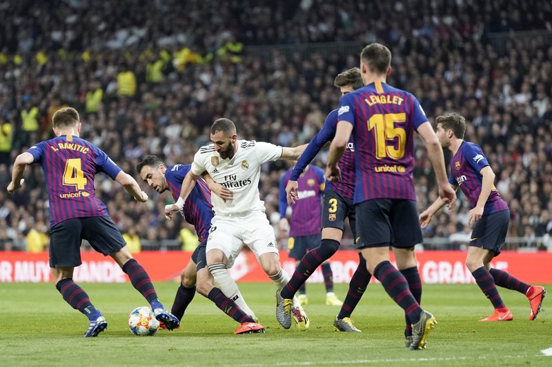 Real forward Karim Benzema fights for the ball with Barcelona players during the Copa del Rey semifinal second leg soccer match between Real Madrid and FC Barcelona at the Bernabeu stadium in Madrid, Spain, Wednesday Feb. (AP Photo/Andrea Comas)