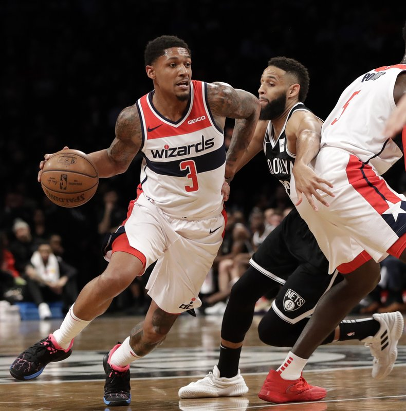 Washington Wizards guard Bradley Beal (3) drives around Wizards forward Bobby Portis (5) with Brooklyn Nets guard Allen Crabbe (33) pursuing during the first half of an NBA basketball game, Wednesday, Feb. (AP Photo/Kathy Willens)