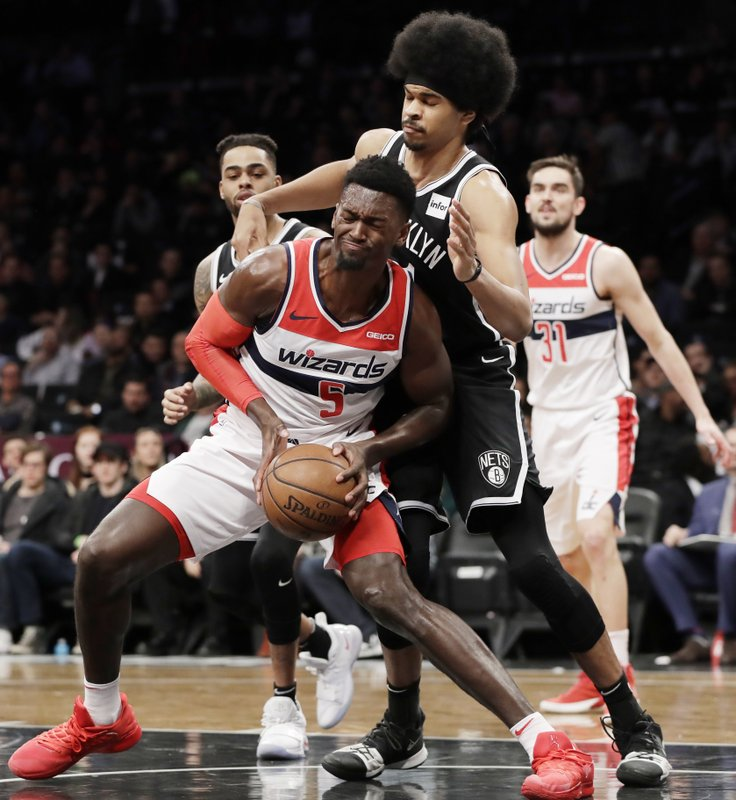 Washington Wizards forward Bobby Portis (5) drives up against Brooklyn Nets center Jarrett Allen (31) as Wizards guard Tomas Satoransky (31) and Nets guard D'Angelo Russell, left rear, watch during the first half of an NBA basketball game, Wednesday, Feb. (AP Photo/Kathy Willens)
