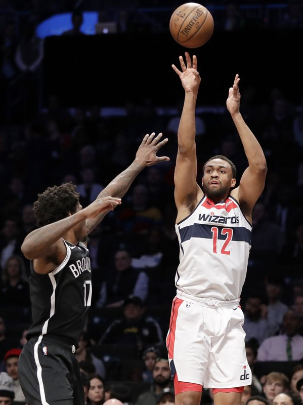 Washington Wizards forward Jabari Parker (12) shoots a three-pointer with Brooklyn Nets forward Ed Davis (17) defending during the first half of an NBA basketball game, Wednesday, Feb. (AP Photo/Kathy Willens)