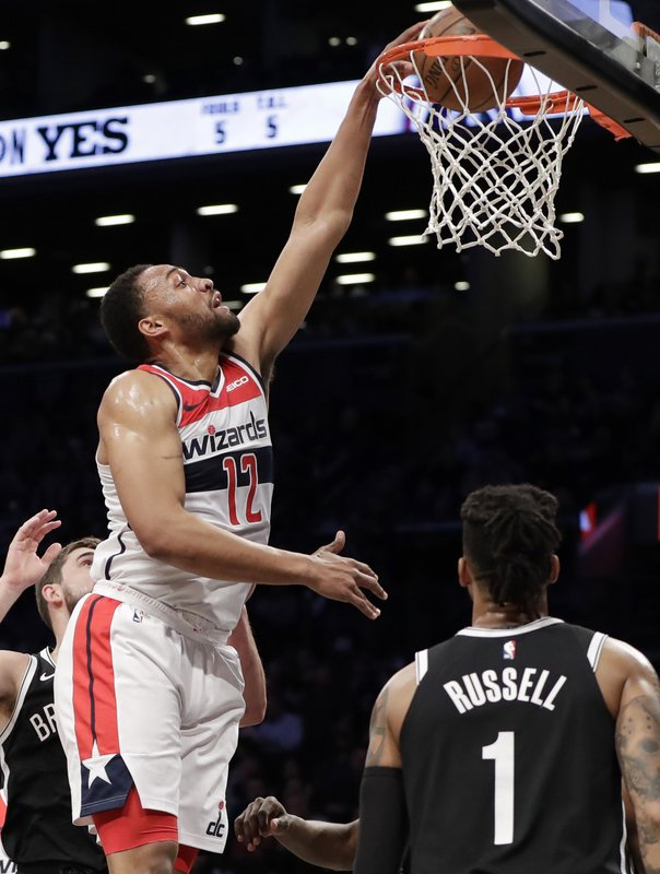 Washington Wizards forward Jabari Parker (12) dunks with Brooklyn Nets guard D'Angelo Russell (1) watching from the floor during the first half of an NBA basketball game, Wednesday, Feb. (AP Photo/Kathy Willens)