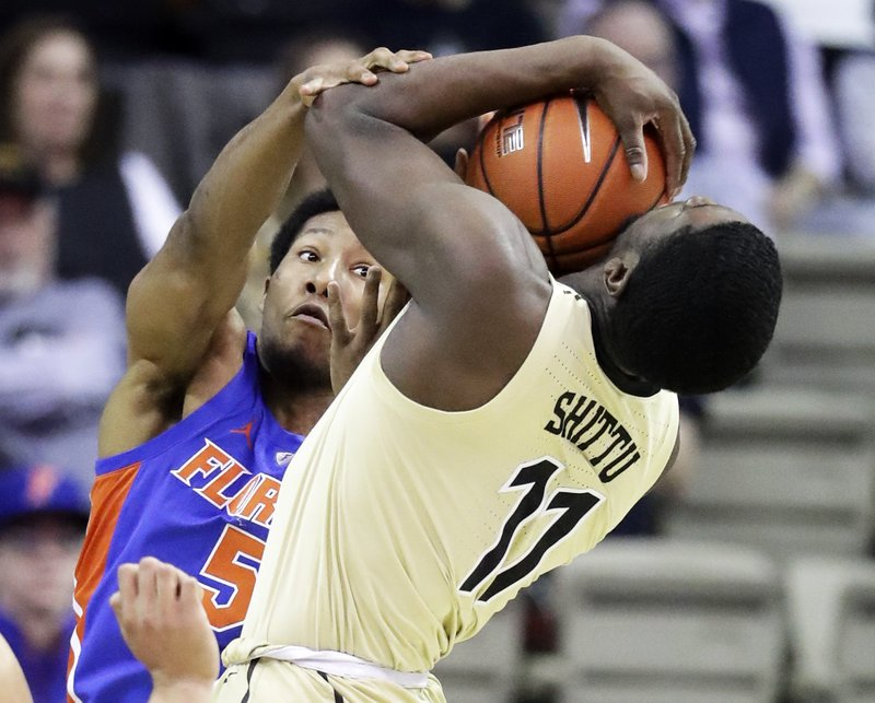 Florida guard KeVaughn Allen (5) fouls Vanderbilt forward Simisola Shittu (11) in the first half of an NCAA college basketball game Wednesday, Feb. (AP Photo/Mark Humphrey)