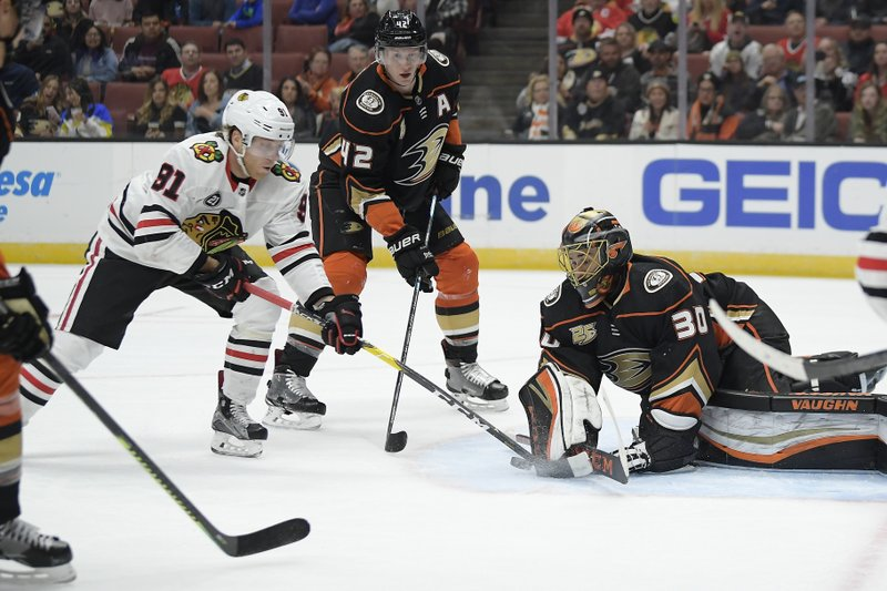 Anaheim Ducks goaltender Ryan Miller, right, stops a shot by Chicago Blackhawks center Drake Caggiula, left, while defenseman Josh Manson helps Miller during the first period of an NHL hockey game Wednesday, Feb. (AP Photo/Mark J. Terrill)