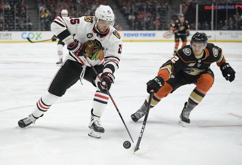 Chicago Blackhawks center Artem Anisimov, left, and Anaheim Ducks defenseman Brendan Guhle chase the puck during the first period of an NHL hockey game Wednesday, Feb. (AP Photo/Mark J. Terrill)
