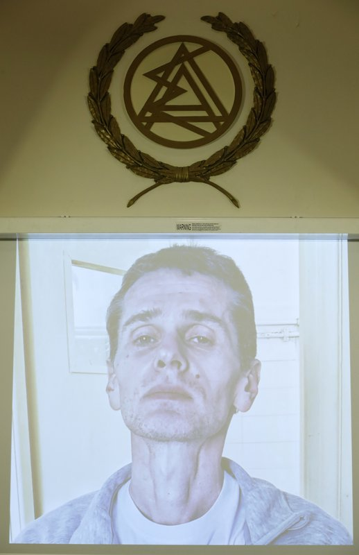 A photograph of the Russian cybercrime suspect Alexander Vinnik is on display on a screen under the logo of Athens Bar Association during a press conference by his lawyers in Athens, Thursday, Feb. (AP Photo/Thanassis Stavrakis)