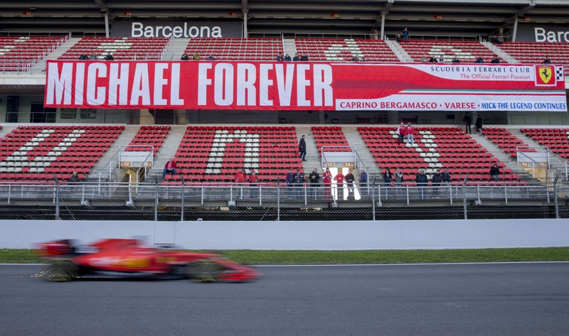 Ferrari driver Charles Leclerc of Monaco drives past a banner in support of former Ferrari driver Michael Schumacher during a Formula One pre-season testing session at the Barcelona Catalunya racetrack in Montmelo, outside Barcelona, Spain, Thursday, Feb. (AP Photo/Joan Monfort)