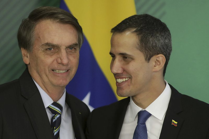 Brazil's President Jair Bolsonaro, left, and Venezuela's self-proclaimed interim president Juan Guaido smile during a joint statement in Brasilia, Brazil, Thursday, Feb. (AP Photo/Lucio Tavora)