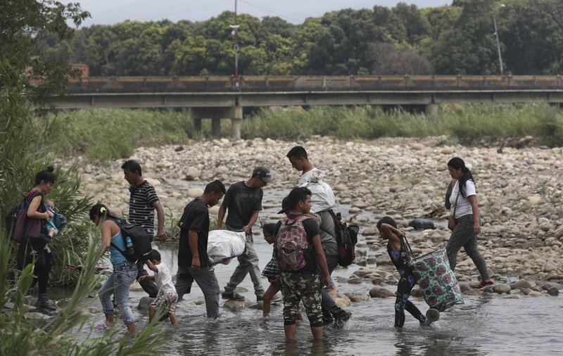 Venezuelans use the Tachira river as a crossing point on the Colombia and Venezuela border, with the Simon Bolivar International Bridge in the background, in La Parada, Colombia, Thursday, Feb. (AP Photo/Martin Mejia)
