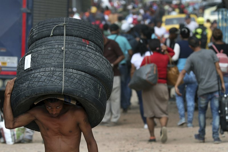 A man carries a set of used tires into Venezuela, through a blind spot on the border near the Simon Bolivar International Bridge in La Parada, Colombia, Thursday, Feb. (AP Photo/Martin Mejia)