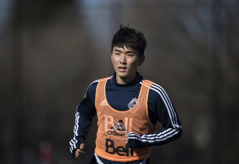 Vancouver Whitecaps midfielder Inbeom Hwang, center, of South Korea, runs during MLS soccer practice  in Vancouver, British Columbia, Tuesday, Feb. (Darryl Dyck/The Canadian Press via AP)