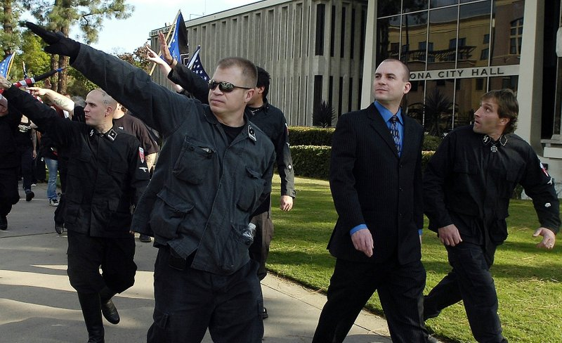 FILE-In this Saturday, Nov. 5, 2011 fule photo, Jeff Schoep, second right in business suit, commander of the National Socialist Movement, leave under police protection after a rally against illegal immigration in Pomona, Calif. (Thomas R. Cordova/The Orange County Register via AP)