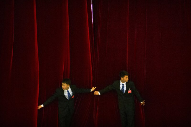 FILE- In this March 15, 2018, file photo, security officials try to keep a curtain closed as delegates leave after the closing session of the Chinese People's Political Consultative Conference (CPPCC) at the Great Hall of the People in Beijing. (AP Photo/Mark Schiefelbein, File)