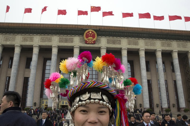 FILE- In this March 4, 2018, file photo, an ethnic minority delegate leaves from the Great Hall of the People on the eve of the annual legislature's opening session in Beijing. (AP Photo/Ng Han Guan, File)