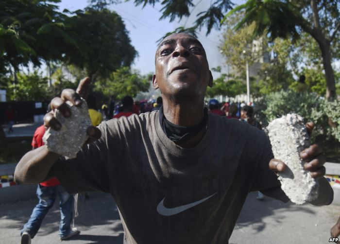 A demonstrator gestures during clashes in front of the National Palace, in th