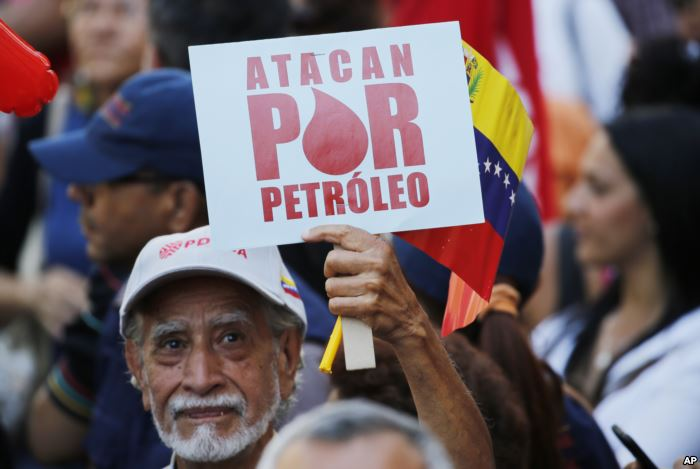 "A man holds a sign that reads in Spanish ""They attack for oil"" duri"
