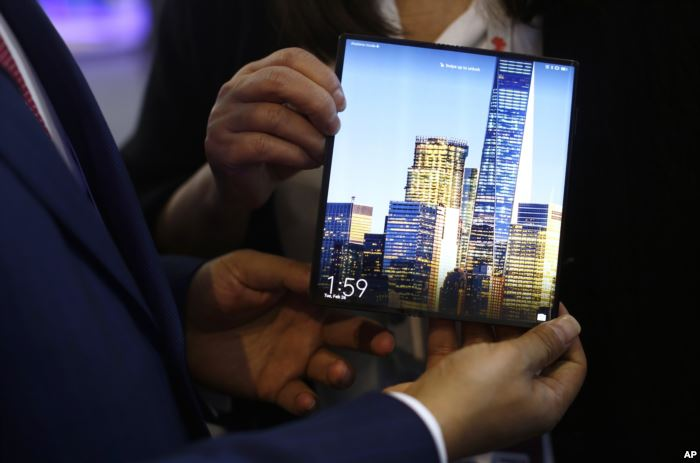 A man holds the new Huawei Mate X foldable 5G smartphone during the Mobile Wo