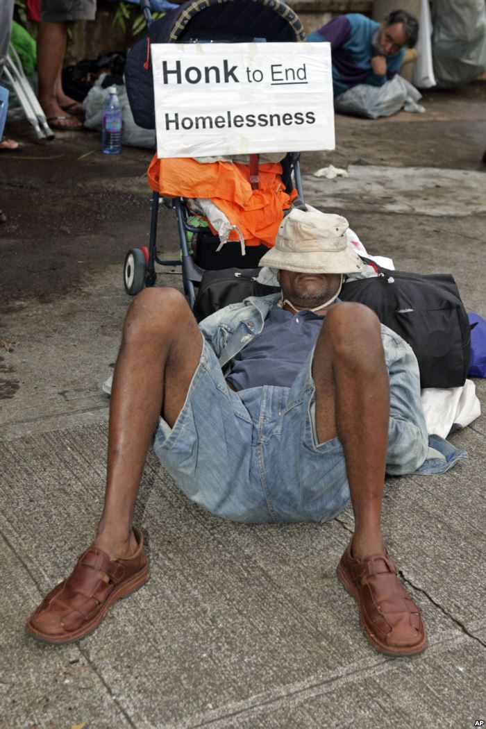 A man sleeps on the sidewalk in front of Honolulu Hale, Tuesday, March 28, 20