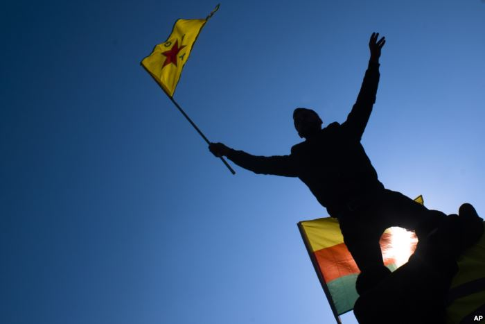 FILE - A man waves a flag with Kurdish symbols as he attends a demonstration