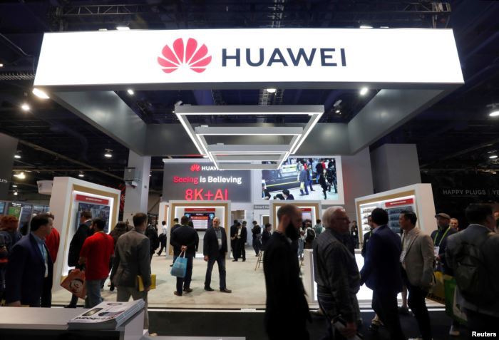 FILE - Attendees pass by a Huawei booth during the 2019 CES in Las Vegas, Nev