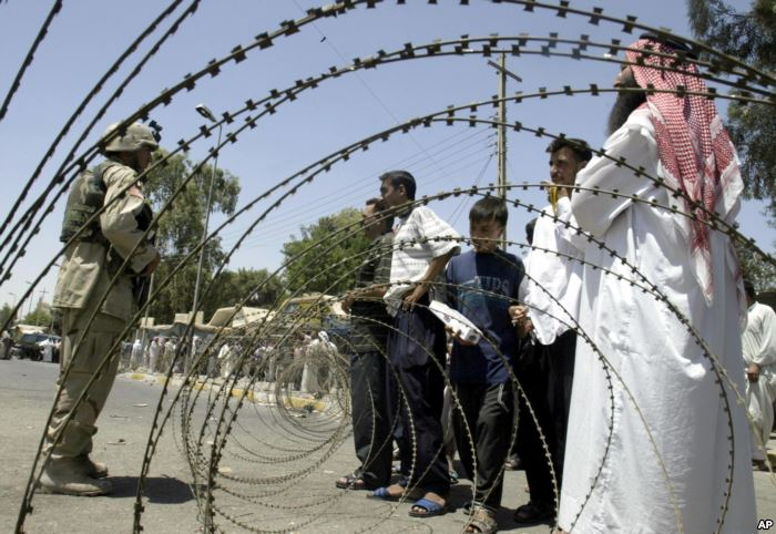 FILE - Iraqis try to persuade a U.S. soldier to enter the central bank in the