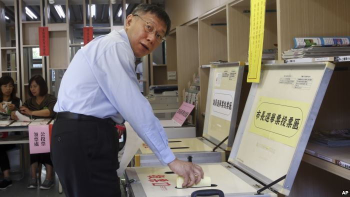 FILE - Taipei Mayor Ko Wen-je casts his ballot at a polling station, Nov. 24,