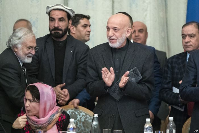 Former Afghan President Hamid Karzai, second from right, applauds during the