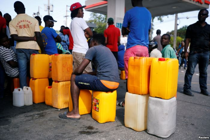 People stand in line waiting to buy fuel, in Port-au-Prince, Haiti, Feb. 13,