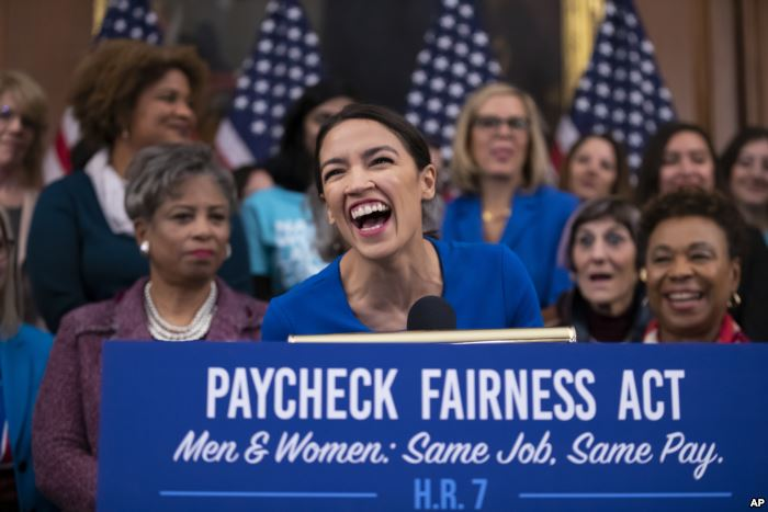 Rep. Alexandria Ocasio-Cortez, D-N.Y., smiles as she speaks at an event to ad